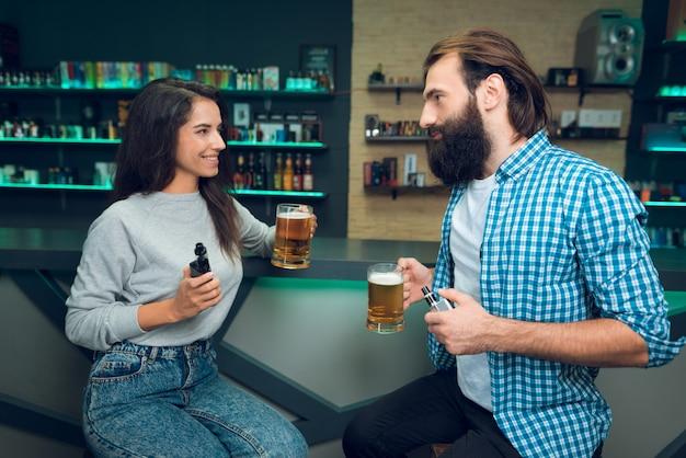 Homem e mulher estão sentados com cerveja e cigarro eletrônico.