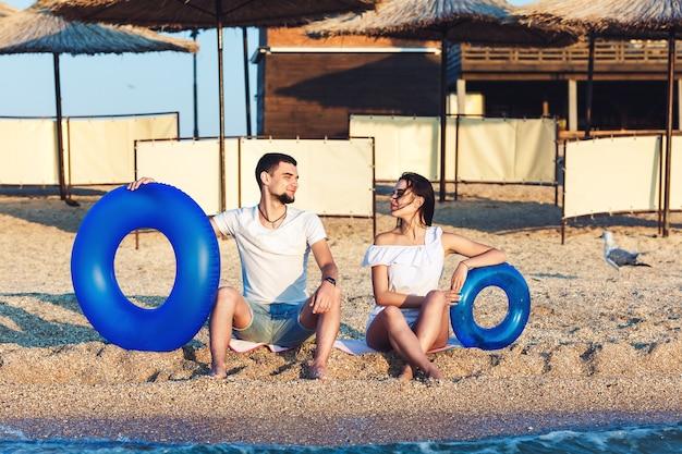 Homem e mulher estão sentados na praia e segurando círculos infláveis. conceito de férias de verão no mar.