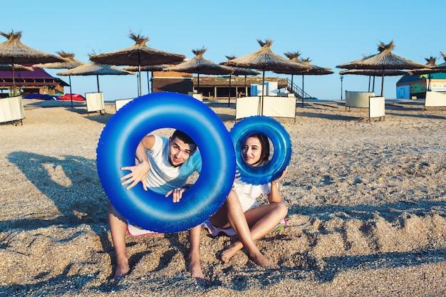 Homem e mulher estão sentados na praia segurando círculos infláveis