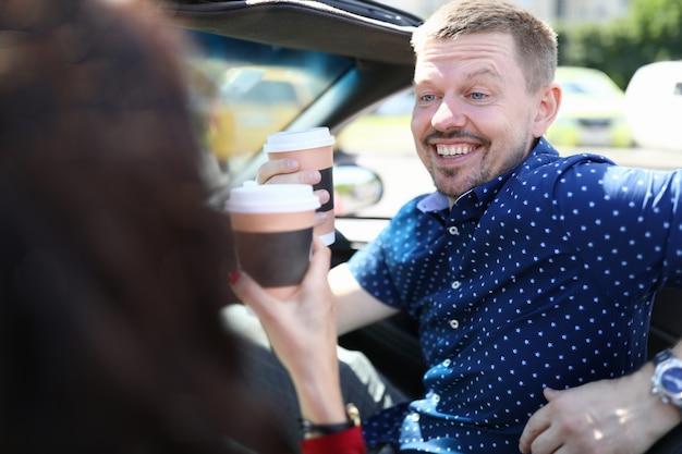 Homem e mulher estão sentados no carro e tomando café