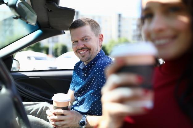 Homem e mulher estão sentados no carro sorrindo e bebendo café