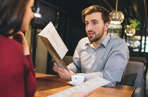 Homem e mulher estão sentados no restaurante e segurando algum menu. eles querem saber o que pedir para comer lá. o homem está dando alguns conselhos alimentares para a mulher.