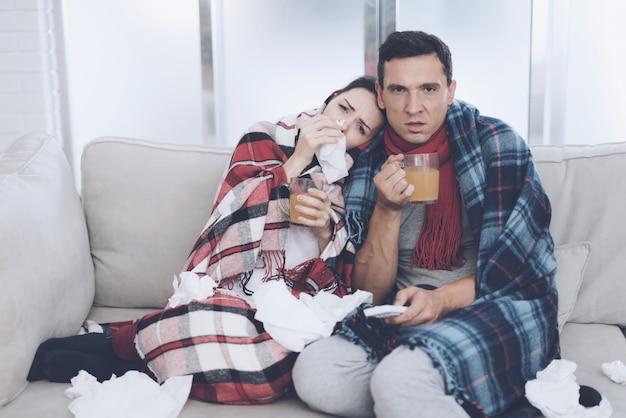 Homem e mulher estão sentados no sofá e tomando chá.