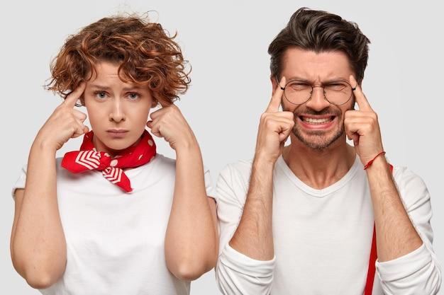 Homem e mulher expressivos em camisetas brancas posando