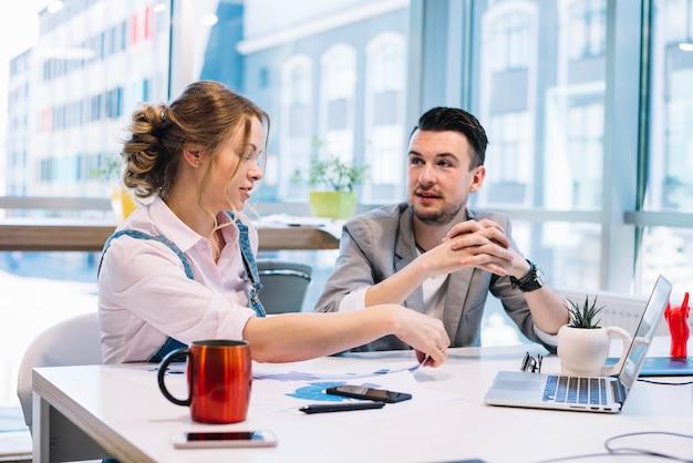 Homem e mulher falando no escritório Foto gratuita