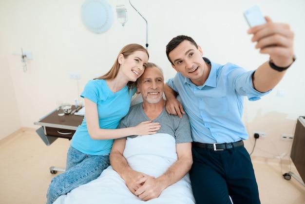 Homem e mulher fazem selfie com o paciente.