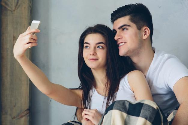 Homem e mulher fazem selfie em casa