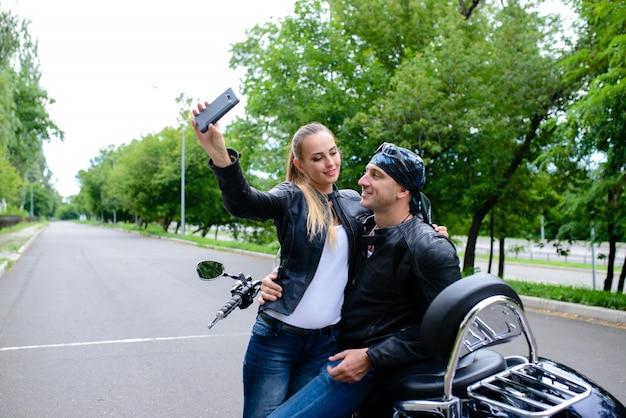 Homem e mulher fazem selfie em uma motocicleta