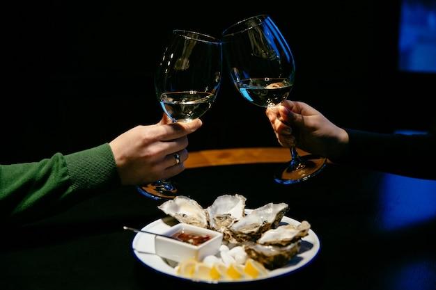 Homem e mulher fazem um elogio com taças de champanhe.