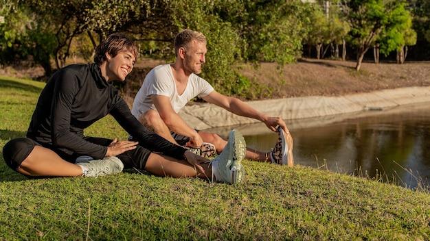 Homem e mulher fazendo aquecimento no parque.