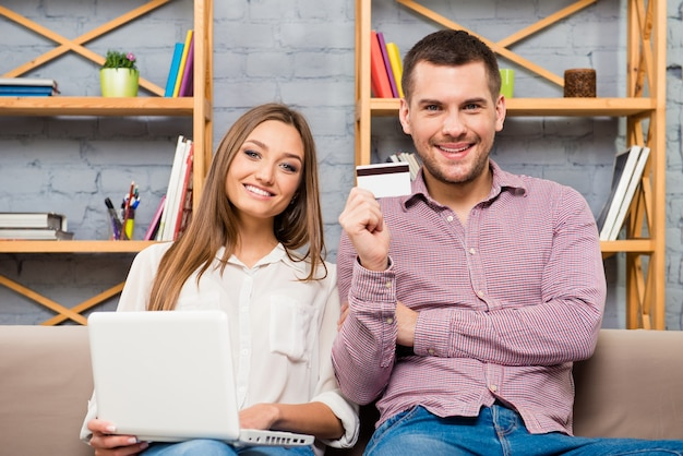 Homem e mulher fazendo compras pela internet com laptop e cartão do banco