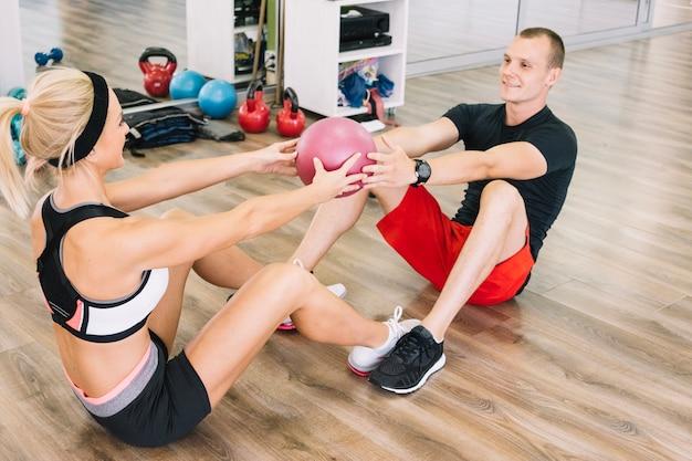 Homem e mulher fazendo exercícios com bola