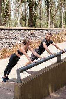 Homem e mulher fazendo flexões juntos ao ar livre