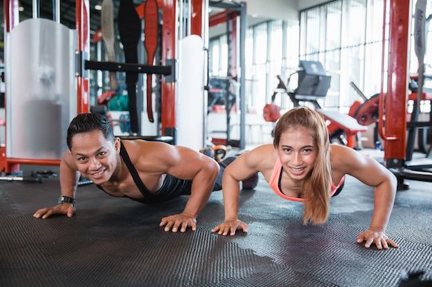 Homem e mulher fazendo flexões