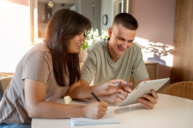 Homem e mulher fazendo lista de compras com tablet