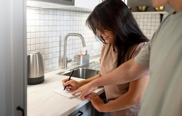 Homem e mulher fazendo lista de compras em casa na cozinha juntos