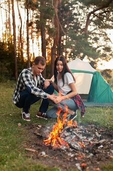 Homem e mulher fazendo uma fogueira ao ar livre
