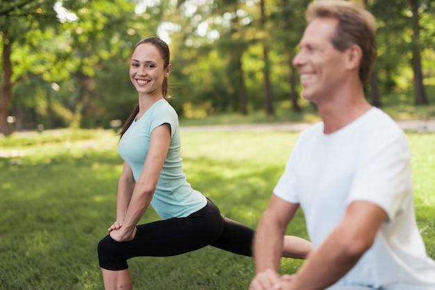 Homem e mulher fazendo warm-up na natureza.