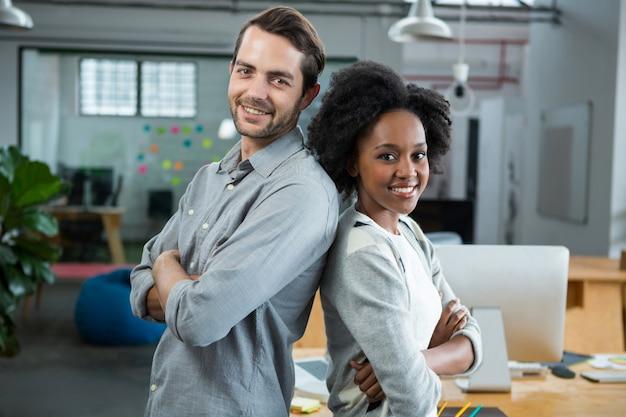 Homem e mulher felizes, de costas um para o outro no escritório