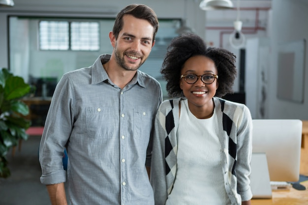 Homem e mulher felizes de pé no escritório