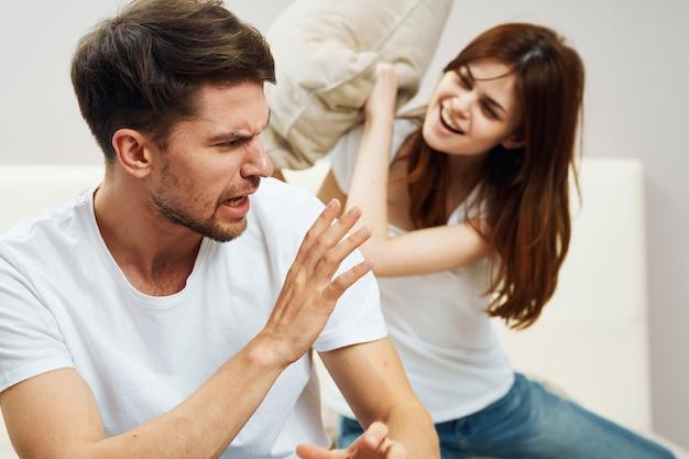 Homem e mulher felizes em uma luta de travesseiros
