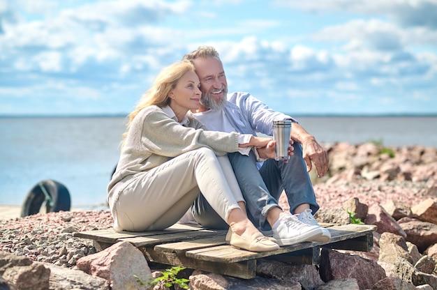 Homem e mulher felizes sentados perto do mar com uma garrafa térmica