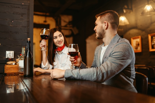Homem e mulher flertando no bar, casal no balcão de madeira.