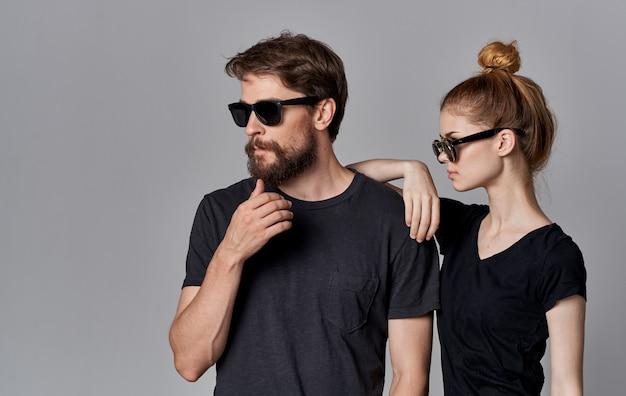 Homem e mulher fofos usando óculos escuros camisetas pretas estilo de vida vista recortada estúdio comunicação