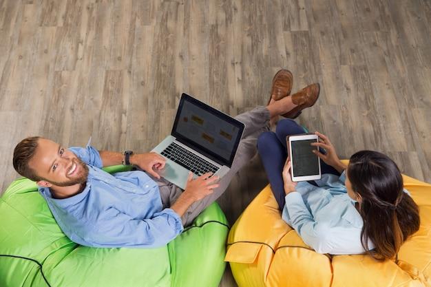 Homem e mulher freelancers trabalhando em cadeiras na moda