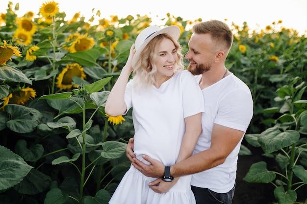 Homem e mulher grávida se abraçam carinhosamente em pé no campo com altos girassóis ao redor deles