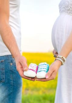 Homem e mulher grávida segurar sapatos de bebê