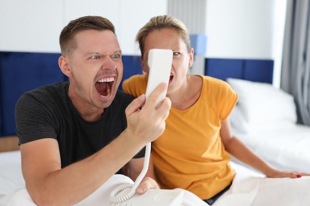Homem e mulher gritando no receptor de telefone em um escândalo de quarto de hotel e serviço precário