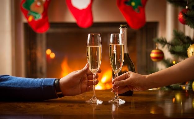 Homem e mulher jantando no natal e tilintando de taças ao lado da lareira a lenha