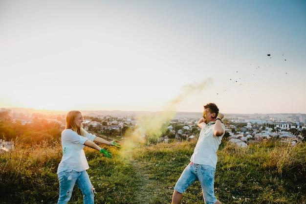 Homem e mulher jogam com fumaça colorida em pé no gramado verde