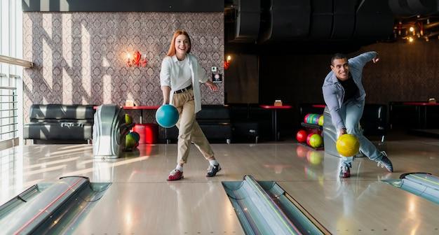 Homem e mulher jogando bolas de boliche no beco