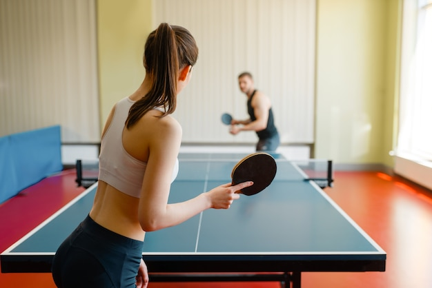 Homem e mulher jogando pingue-pongue dentro de casa