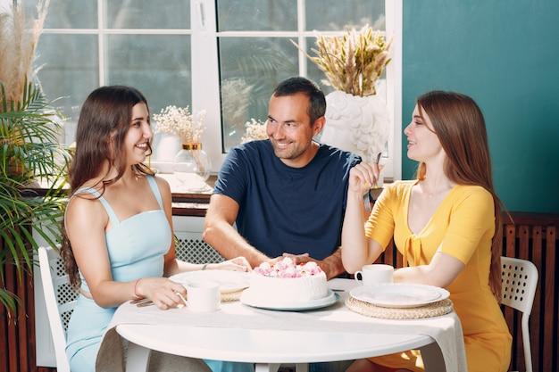 Homem e mulher jovem sentar na cozinha de apartamento em casa com bolo na mesa e comemorando o aniversário.