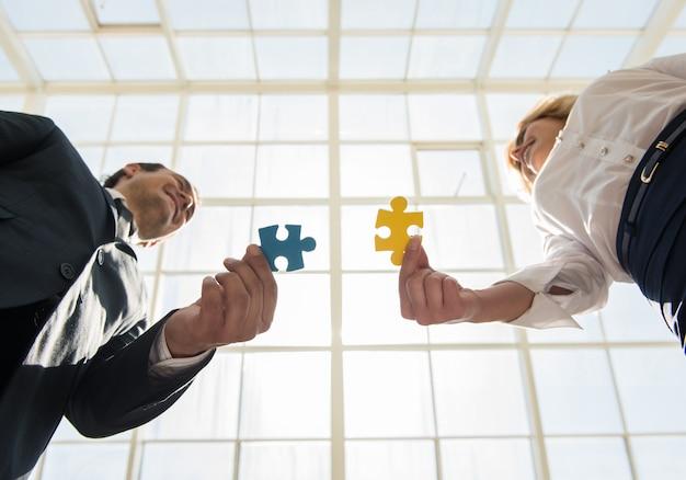 Homem e mulher, juntando peças de puzzle de quebra-cabeça.