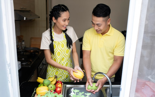 Homem e mulher lavando frutas