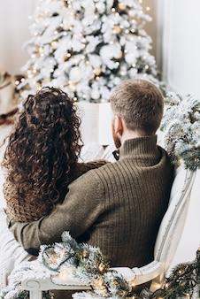 Homem e mulher lendo um livro juntos no fundo da árvore de natal