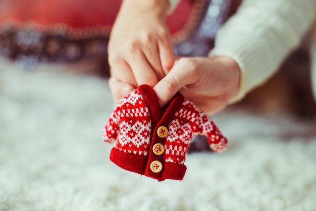 Homem e mulher mantêm em suas mãos suéter para bebê recém nascido