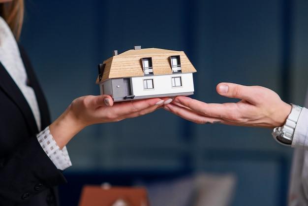 Homem e mulher mãos segurando um modelo 3d da casa.