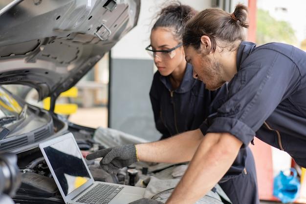 Homem e mulher mecânicos usando laptop enquanto verificam e consertam a manutenção de um carro na garagem de serviço