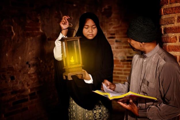 Homem e mulher muçulmanos lendo o alcorão, na velha mesquita de ayutthaya, tailândia