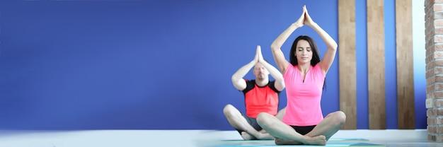 Homem e mulher na academia estão sentados em posição de lótus