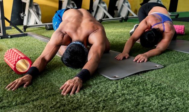 Homem e mulher na academia fazendo abdominais