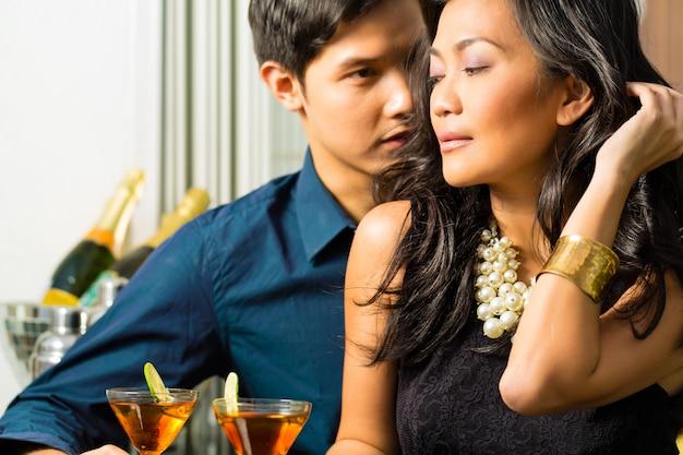 Homem e mulher na ásia no bar com cocktails
