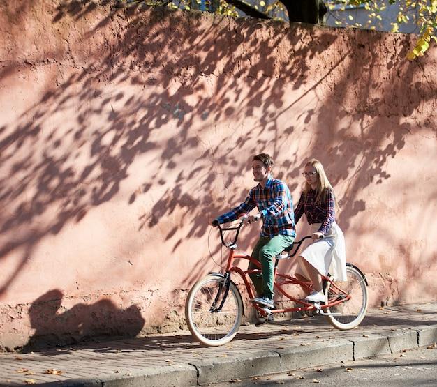 Homem e mulher na bicicleta tandem na parede vermelha