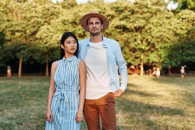 Homem e mulher na natureza no parque andam e conversam.