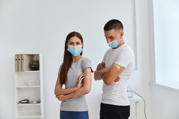 Homem e mulher na recepção do hospital com camadas bactericidas nos ombros cobiçosos